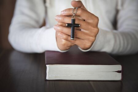 A cross in the hands of a young woman blessing on the scriptures from God with the power and power of holiness, which brings luck and the power of religion, faith, worship, Christian thought.