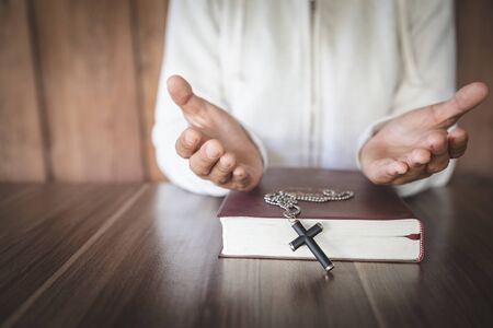 A young woman prayed with the palm upside down. Top bible books Considered as a sacred blessing of God In the church, the concept of spirituality and worship and praise of Christians.