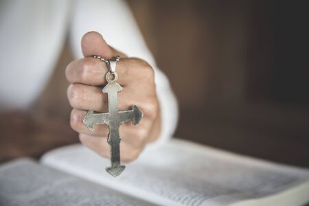 In the hands of the young lady there was a cross and placed in the Bible. Considered as the sacred blessing of God, spirituality and worship and praise from Christians religious beliefs for blessings.