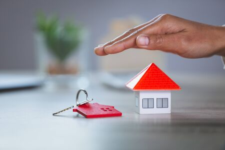 Orange house and keys And with his hands protecting The concept of home protection using the gestures and symbols of real estate investors, credit care and contracts.