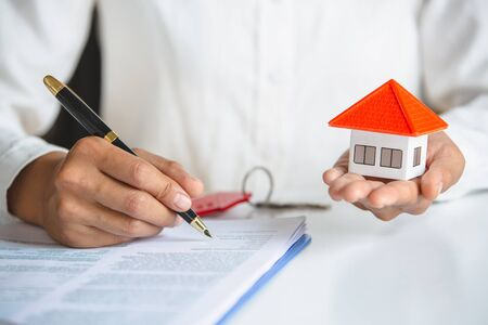 Business people and customers are signing a contract to buy a house Hand holding a pen,signing purchase contract And there is a house with orange roofs laid on the hands The concept of buying a house.