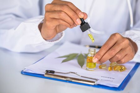 Researchers or doctors are about to drop CBD hemp oil in a glass bottle near a prescription. CBD Cannabis Oil Treatment Concept Natural herbs that extract oil for treatment
