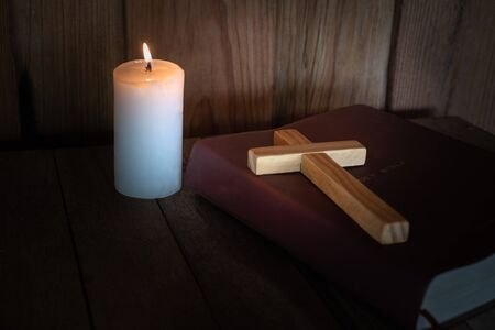 The crucifix lay on the bible. While there are candles that are illuminating Christian religious concepts, the crucifixion of faith and faith in God.