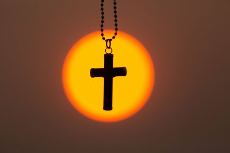 The crucifix in the middle of the sunrise or sunset. The concept of Christianity, a blessing from prayer to Jesus. Belief in God, pray for God's struggle and victory.