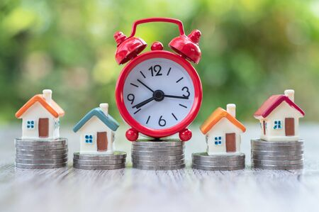 Red alarm clock And coin stairway houses Financial concepts, savings, investments in finance, accounting and the stock market are worth the time spent investing.