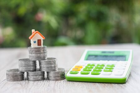 Small model house with orange roof on stack of coins Concepts of saving money, business growth, saving money for investment Save money for future housing, mortgage tax.