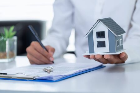 Gray roof house on the hands of businessmen or agents And signing the purchase contract House trading ideas Home insurance, investment, rental or purchase Real Estate and Mortgages.