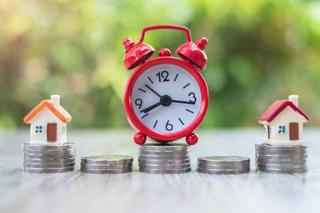 Red alarm clock on a coin. House on a coin. The concept of time and financial risk. Business investment should take appropriate time. Accounting and marketing.