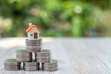 Houses on stacks of coins that are arranged in a triangle Loan concept by money house from coins, business, finance and money Successful financial business Economical for small real estate projects.