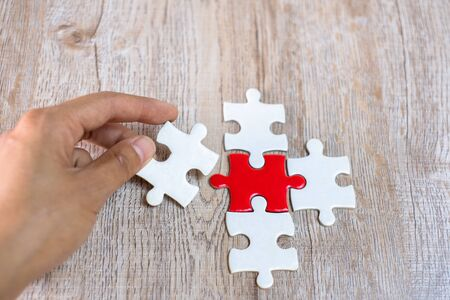 The white jigsaw handle is going to be put in order to make the excess pieces complete the jigsaw. Cooperation concept Business background Business success strategies.