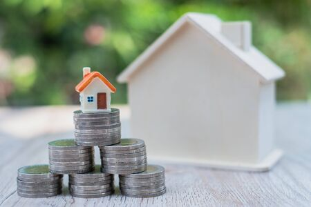 A small house on a pile of coins laid in a triangle The concept of real estate growth Investment and risk management Saving money buying a house.
