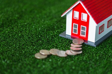 The red roof house laying on the green grass. And with coins placed as a walkway Ideas to save money on new home purchases or loans for real estate investment planning Home insurance. Banque d'images