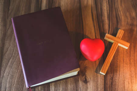 Bible, cross, symbol and red heart Candle light Symbol of supplication and faith The Study of Christ Believing in God, escape, there is a space to enter a message. Archivio Fotografico