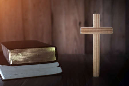 The cross is placed near A pile of bible books While there are candles that illuminate the Christian religious concept, the crucifixion of faith and faith in God.