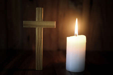 The Crucifix and Candle Light provide a light for Bible study, Christian religious concept, the crucifixion of faith and faith in God. Supplication to study the scriptures.
