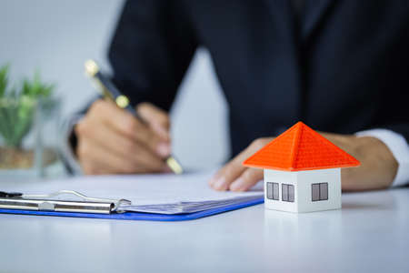 Orange roof house and investor businessman are contracting to buy a house. Real Estate Agent Concept Satisfied with home purchase mortgage contract Choosing a house and residence.