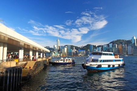 Hong Kong pier and skyline, there are many ships crossing Victoria Harbour per day.