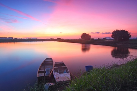 Sunset along the pond with isolated boats