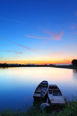 Sunset along the pond with two boats photo