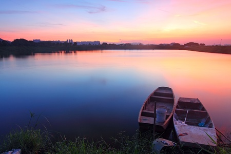 Sunset along the pond with isolated boats photo