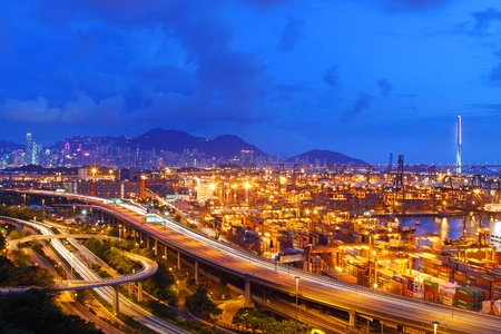 Busy traffic in Hong Kong at night with container terminal background