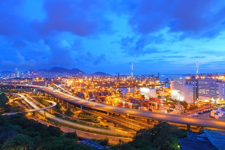 Traffic in Hong Kong at night, with container terminal background.