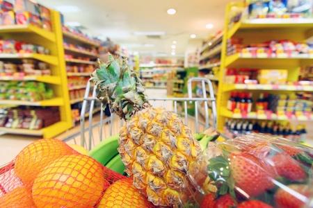 departamentos: Mover cesta de la compra en el supermercado. Fue tomada con una velocidad de obturaci�n lenta del comprador Foto de archivo