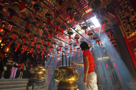 mococa: HONG KONG - 26 Jul, Man Mo temple in Hong Kong with many incense coils and tourists on 26 July, 2011. It is a very famous temple in Hong Kong for the worship of the civil or literature god Man Tai. It was graded as a Grade I historic building in 1993 and