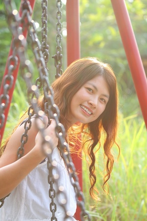 A beautiful and cheerful asian girl playing swing Stock Photo - 11988778