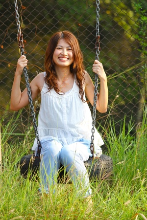 Asian girl playing swing in a park photo