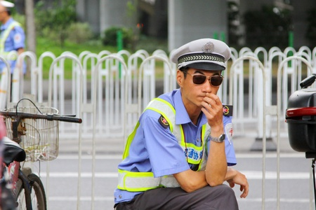 GUANGZHOU - APR 22, A policeman works along the street in Guangzhou, China on 22 April, 2011.