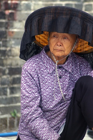 HONG KONG - FEB 22, A Hakka old woman in Kat Hing Wai of Hong Kong on 22 Feburary, 2009. They speak the Cantonese dialect Weitou dialect, rather than Hakka. Stock Photo - 12935821