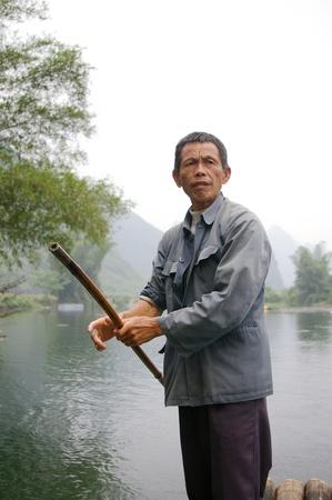 CHINA - MAY 16, A fisherman is paddling the bamboo boat along the Yulong River in Guilin, China on 15 May, 2010. Stock Photo - 12935757