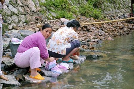 CHINA - MAY 17, Chinese woman is washing clothes along Li River in Yangshuo, China on 17 May, 2010.