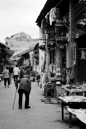 CHINA - MAY 17, An old woman is walking along the traditional street in Xingping, Yangshuo, China on 17 May, 2010.