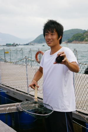 HONG KONG - SEPT 12, A young fisherman is introducing the fishing village to public on 12 September, 2009.