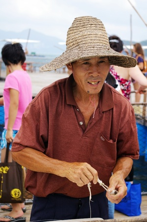 HONG KONG - SEPT 12, A traditional Chinese fisherman is making net on Lamma Island, Hong Kong on 12 September, 2009. Stock Photo - 12935789