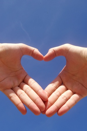 Man hands forming a heart over the blue sky  photo