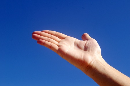 Giving hand under blue sky photo