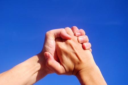 Holding hands under blue sky photo
