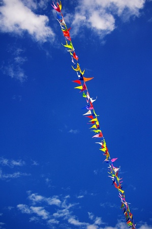 Multi colored party flags on a line on a background of blue sky with fluffy white clouds  photo