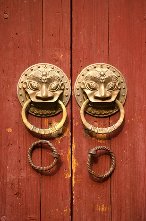 Double lion knobs on an old wooden gate photo