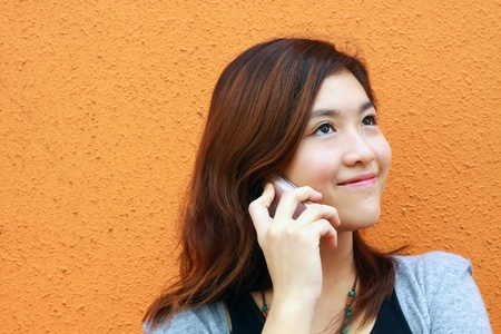 Asian woman calling and talking on phone photo