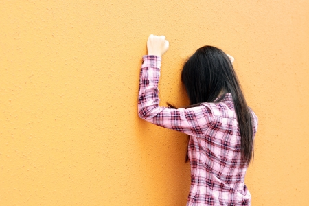 Asian woman very sad and facing the wall photo