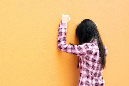 Asian woman very sad and facing the wall