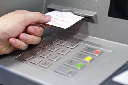A hand taking a receipt of an Automated Teller Machine Stock Photo