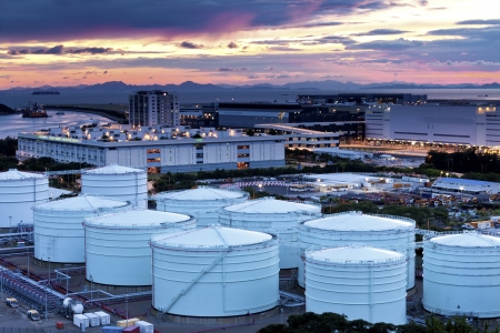 atmosphere construction: Oil and gas refinery tanks at twilight