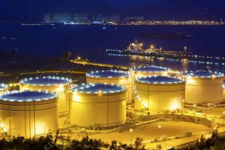 夜の製油所で大きな産業石油タンク 報道画像