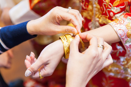 bride bangle: Elderly relatives presenting the golden bracelet as a blessing in chinese wedding