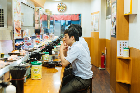 TOKYO - AUG 8: People eat at a sushi bar on August 8, 2015 in Tokyo. With about 160,000 restaurants, Tokyo is the city with most restaurants in the world.